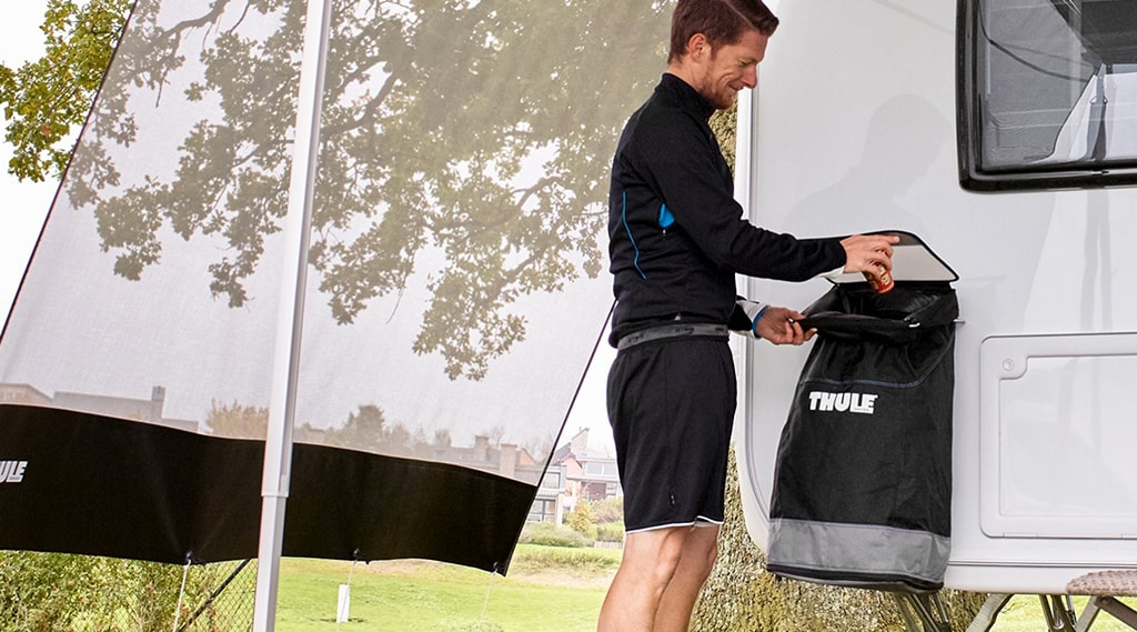 Man attaching a Thule Trash Bin to his RV