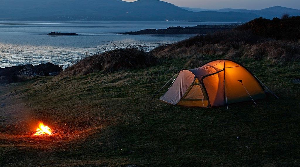 Dome Tent setup near a lake with a bonfire closeby
